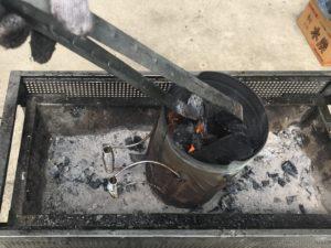 火起こし壺から炭を取り上げる写真